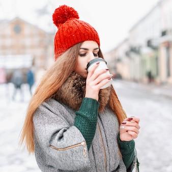 Junges schönes mädchen, das heißen winter im kalten wintertag trinkt