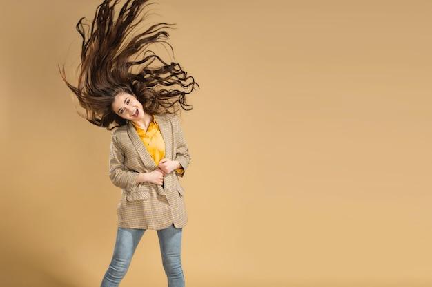 Junges schönes mädchen, das langes fließendes haar auf pastellorange winkt.