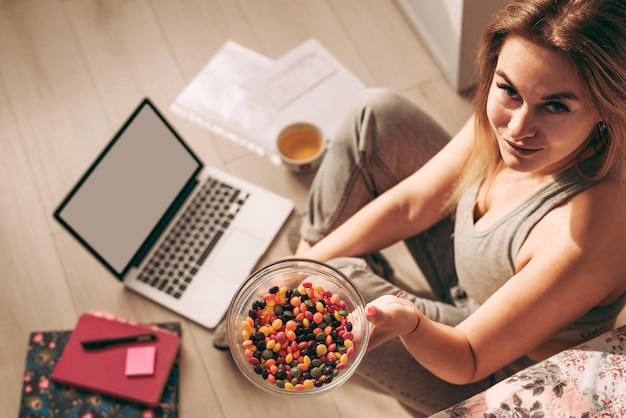 Junges schönes mädchen, das mit ihrem laptop und einigen notizbüchern und papieren bunte süßigkeiten genießt