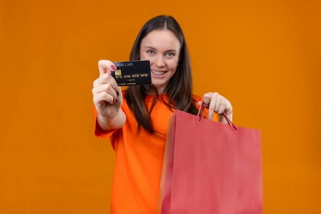 Junges schönes mädchen, das orange t-shirt hält papierpaket zeigt kreditkarte lächelnd fröhlich stehend über isoliertem orange hintergrund