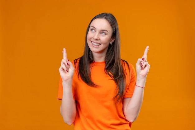 Junges schönes mädchen, das orange t-shirt trägt, wünschenswert wünschenswert mit kreuzenden fingern lächelnd fröhlich stehend über isoliertem orange hintergrund