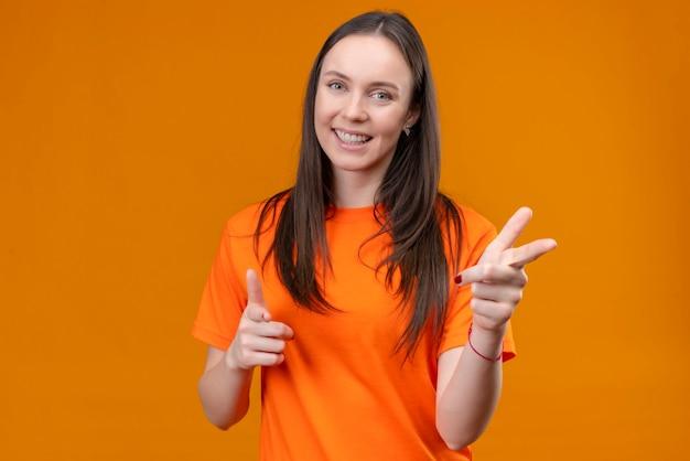 Junges schönes mädchen, das orange t-shirt trägt, zeigt auf kamera lächelnd fröhlich positiv und glücklich stehend über lokalisiertem orange hintergrund