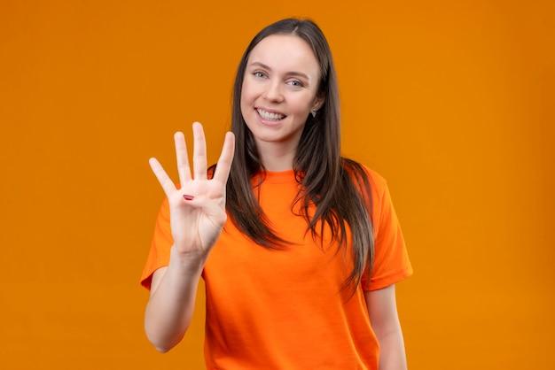 Junges schönes mädchen, das orange t-shirt zeigt und mit den fingern nummer vier zeigt, die über lokalisiertem orange hintergrund stehen