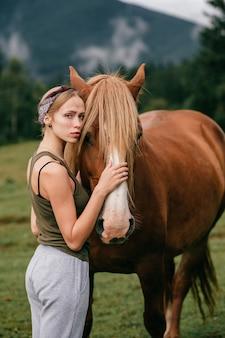 Junges schönes mädchen, das pferd an der natur umarmt