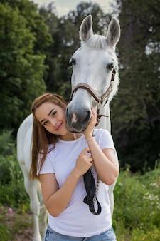 Junges schönes mädchen, das pferd an natur umarmt. pferdeliebhaber.