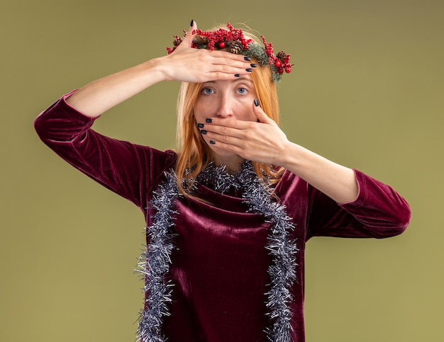 Junges schönes mädchen, das rotes kleid mit kranz und girlande am hals trägt, bedeckt mit händen stirn und mund lokalisiert auf olivgrüner wand