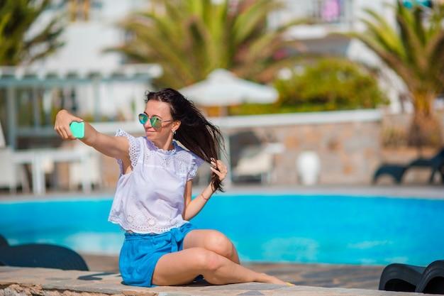 Junges schönes mädchen, das selfie am rand des swimmingpools an den sommerferien nimmt