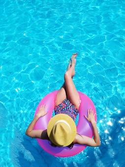 Junges schönes mädchen, das sich entspannt und im blauen schwimmbad mit einer rosa kreisnahaufnahme schwimmt