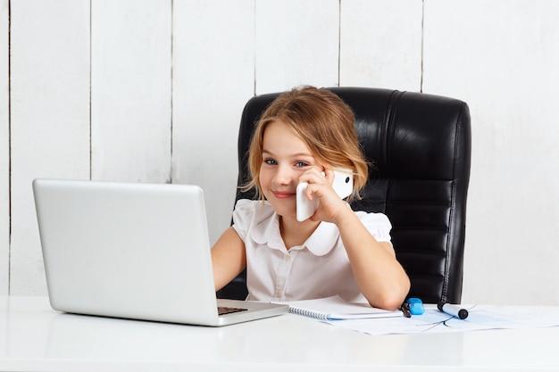 Junges schönes mädchen, das telefon am arbeitsplatz im büro spricht.