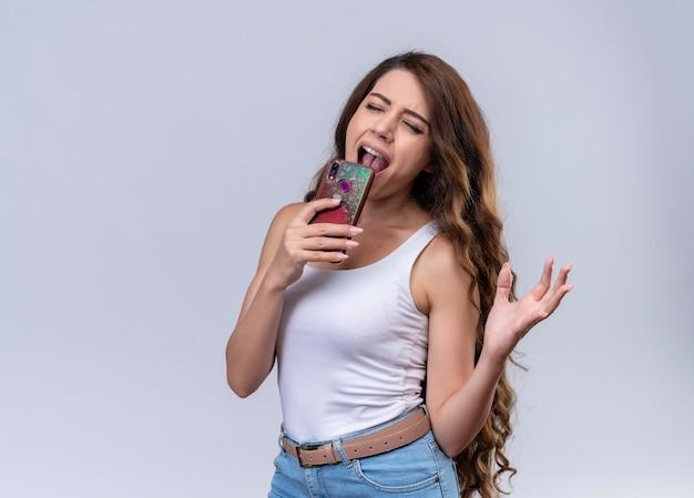 Junges schönes mädchen, das unter verwendung des mobiltelefons als mikrofon mit geschlossenen augen auf isolierter weißer wand mit kopienraum singt