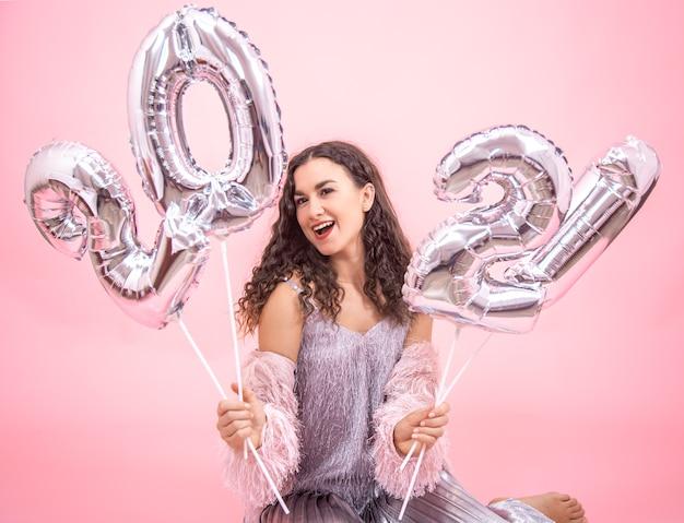 Junges schönes mädchen freut sich im neuen jahr auf einem rosa hintergrund mit silbernen luftballons für das neujahrskonzept