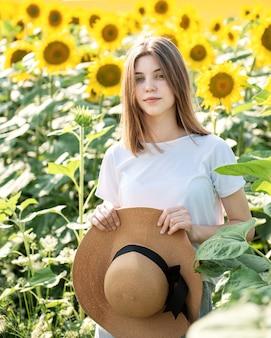 Junges schönes mädchen geht im sommer auf einem feld mit blühenden sonnenblumen