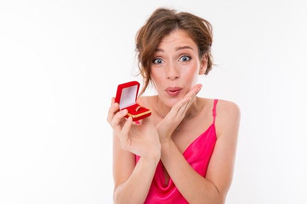 Junges schönes mädchen hält einen kasten für einen verlobungsring und freut sich