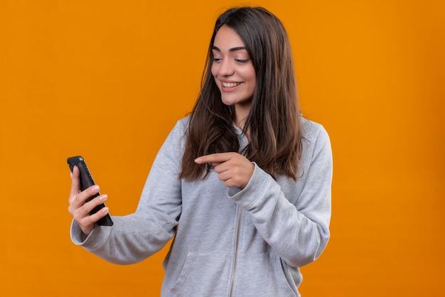 Junges schönes mädchen im grauen kapuzenpulli, der telefon hält und auf telefon zur gleichen zeit schaut, um mit lächeln auf gesicht zu stehen, das über orange hintergrund steht