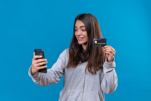 Junges schönes mädchen im grauen kapuzenpulli, der telefon hält und die kreditkarte zum telefon zeigt, kam mit lächeln auf gesicht, das über blauem hintergrund steht