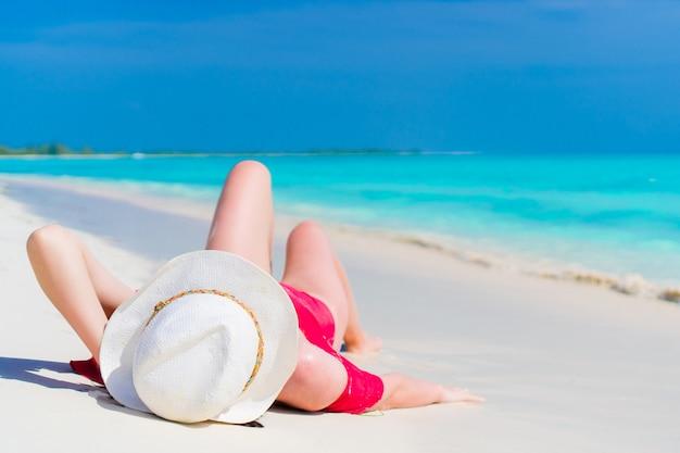 Junges schönes mädchen im hut, der auf dem strand am seichten tropischen wasser liegt