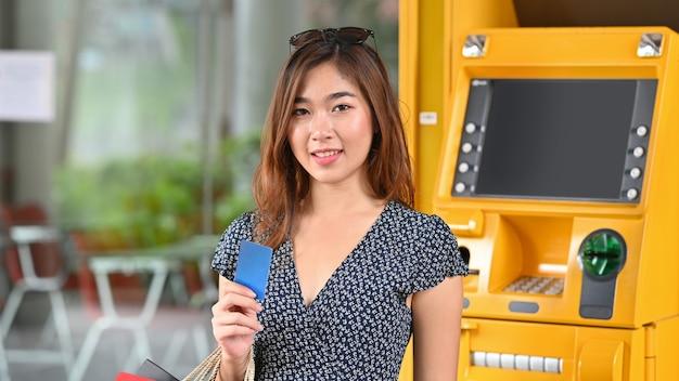 Junges schönes mädchen im kleid, das eine kreditkarte und einkaufstaschen in ihren händen hält, während neben dem gelben geldautomaten im erdgeschoss des modernen einkaufszentrums steht.