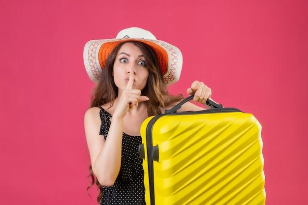 Junges schönes mädchen im kleid im tupfen im sommerhut, der koffer hält, der kamera betrachtet, die stille geste mit finger auf lippen macht, die über rosa hintergrund stehen