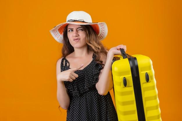 Junges schönes mädchen im kleid im tupfen im sommerhut stehend mit koffer, der beiseite missfällt über gelbem hintergrund