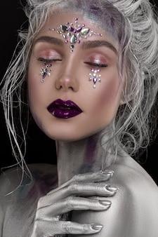 Junges schönes mädchen im silbernen make-up mit bergkristall