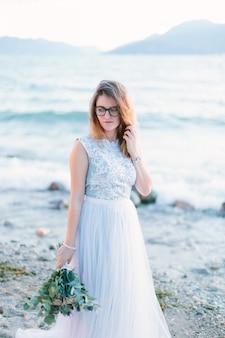 Junges schönes mädchen in den gläsern und im blauen kleid, das nahe dem see geht. lago di garda in sirmione. italien