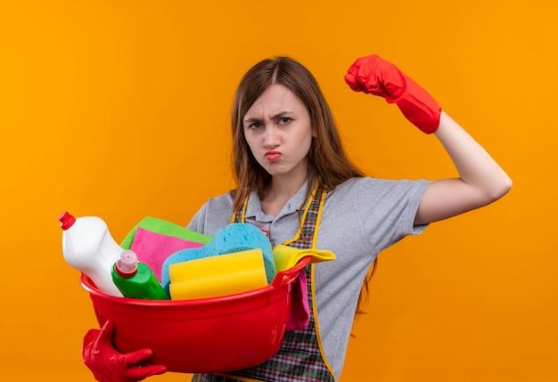Junges schönes mädchen in der schürze und in den gummihandschuhen, die becken mit reinigungswerkzeugen halten, die faust heben, die langlebig aussieht, sel zufrieden, bereit zu reinigen