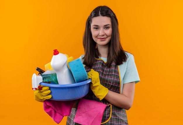 Junges schönes mädchen in der schürze und in den gummihandschuhen, die becken mit reinigungswerkzeugen halten, die freundlich kamera betrachten lächeln
