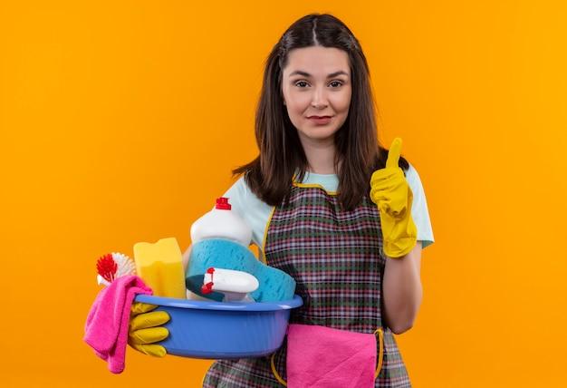 Junges schönes mädchen in der schürze und in den gummihandschuhen, die becken mit reinigungswerkzeugen halten, die freundlich lächelnd daumen zeigen