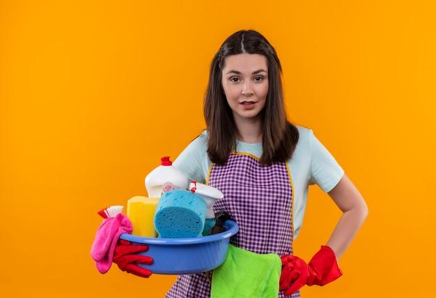 Junges schönes mädchen in der schürze und in den gummihandschuhen, die becken mit reinigungswerkzeugen halten, die kamera mit sicherem ausdruck betrachten