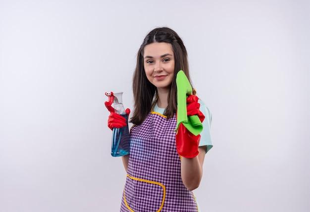 Junges schönes mädchen in der schürze und in den gummihandschuhen, die reinigungsspray und teppich halten, die zuversichtlich lächeln, bereit für die reinigung