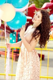 Junges schönes mädchen in einem kleid und lockigem haar hält bunte luftballons in ihren händen und geht in einem vergnügungspark im sommer