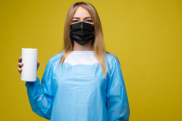 Junges schönes mädchen in einem medizinischen wegwerfkleid und mit einer maske auf ihrem gesicht hält nasse antibakterielle tücher, porträt lokalisiert auf gelbem hintergrund