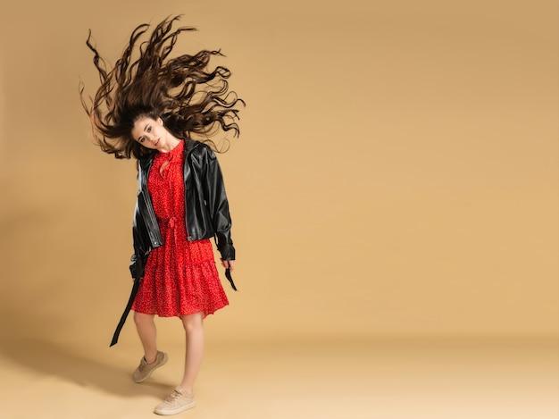 Junges schönes mädchen in einem roten kleid mit tupfen und einer schwarzen lederjacke, die ihr langes fließendes haar auf einem pastellorange wedelt.