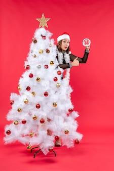 Junges schönes mädchen in einem schwarzen kleid mit weihnachtsmannhut, der sich hinter weihnachtsbaum versteckt und uhr hält, die ok geste macht