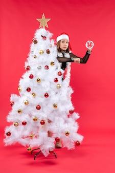 Junges schönes mädchen in einem schwarzen kleid mit weihnachtsmannhut, der sich hinter weihnachtsbaum versteckt und uhrzeit hält