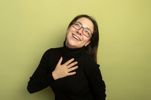Junges schönes mädchen in einem schwarzen rollkragenpullover und in den gläsern, die hand auf ihrer brust halten, die positive gefühle fühlen