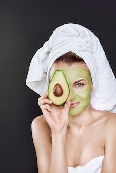 Junges schönes mädchen in einem weißen tuch auf ihrem kopf mit einer kosmetischen maske der avocado auf ihrem gesicht.