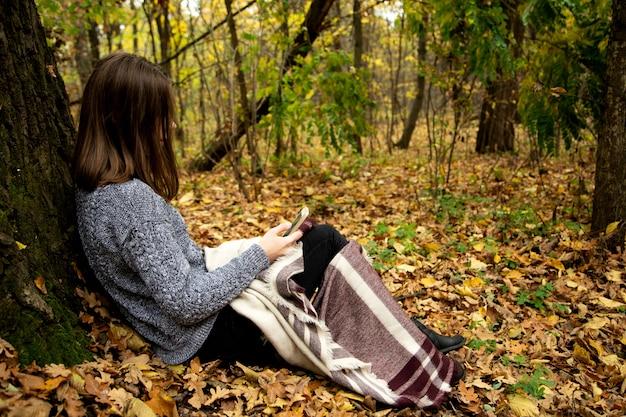 Junges schönes mädchen in einer grauen jacke, die im herbstwald nahe einem großen baum mit einem handy sitzt