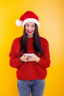 Junges schönes mädchen in einer roten weihnachtsmütze hält ein telefon in seinen händen weihnachtsrabattinhalt