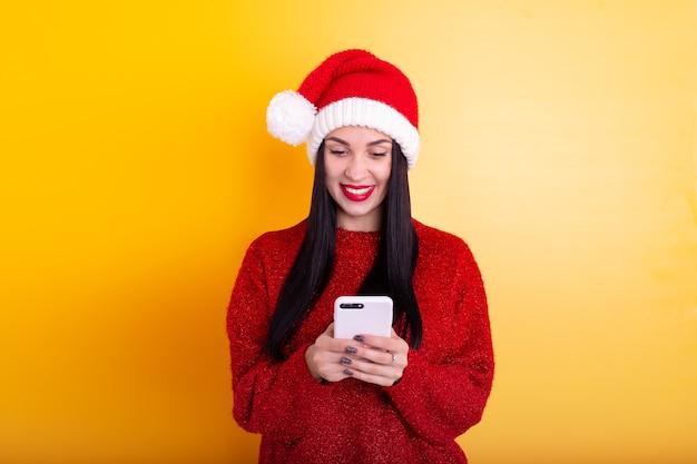 Junges schönes mädchen in einer roten weihnachtsmütze hält ein telefon in seinen händen