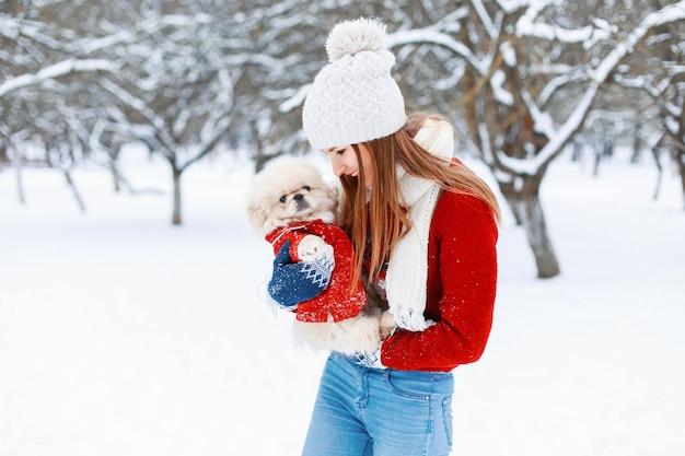 Junges schönes mädchen in einer warmen winterkleidung spielt mit einem welpen in ihren armen im park