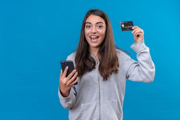 Junges schönes mädchen in grauem kapuzenpulli, das kamera mit lächeln auf gesicht und gleichem halten des telefons und der kreditkarte betrachtet, die über blauem hintergrund stehen