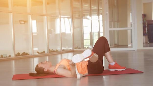 Junges schönes mädchen in sportkleidung beim aufwärmen auf dem teppich in der turnhalle mit klebeband, sonnenlicht