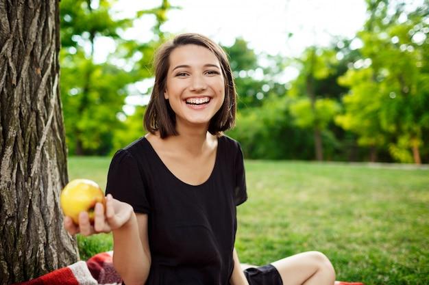 Junges schönes mädchen lächelnd, apfel auf picknick im park haltend.