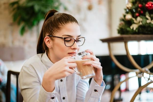 Junges schönes mädchen mit brillen kaffee am café genießend.