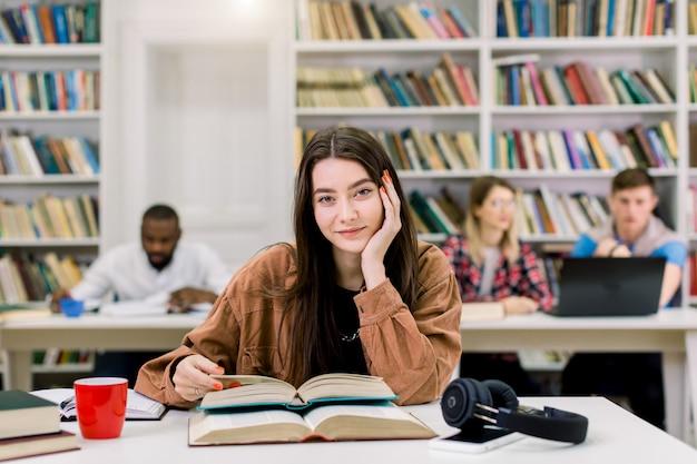 Junges schönes mädchen mit dem geraden langen dunklen haar, das im braunen hemd trägt, am tisch in der bibliothek sitzt und sich auf test oder prüfung vorbereitet, bücher liest