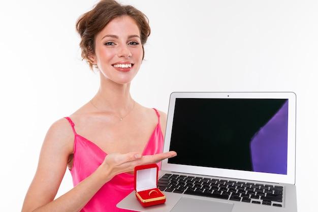 Junges schönes mädchen mit dem gewellten braunen ausgebesserten haar, sauberer haut, den flachen zähnen, schönem lächeln, im rosa trikot, hält einen trainingsringkasten und einen laptop
