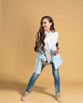 Junges schönes mädchen mit dem langen fließenden haar in einem weißen hemd und in der blauen jacke, die auf einem pastellorange aufwerfen.