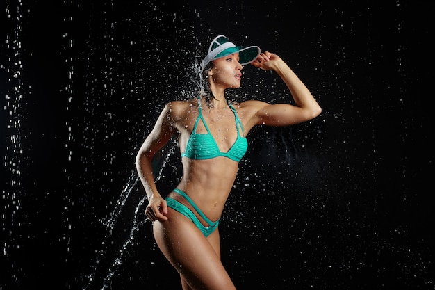 Junges schönes mädchen mit einem dünnen athletischen körper kleidete in einem tadellosen grünen bikini an, der auf einem schwarzen hintergrund aufwirft