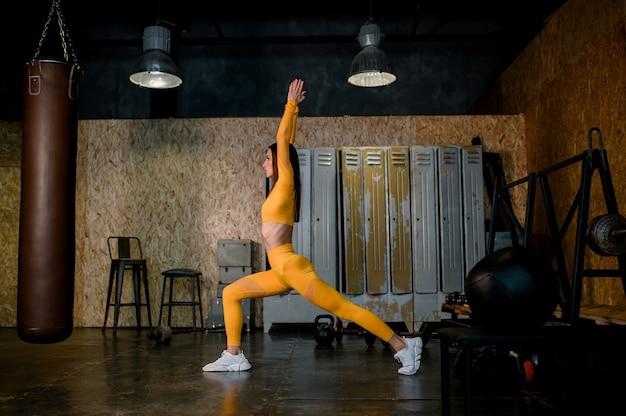 Junges schönes mädchen mit gelbem sportanzug, der yoga tut